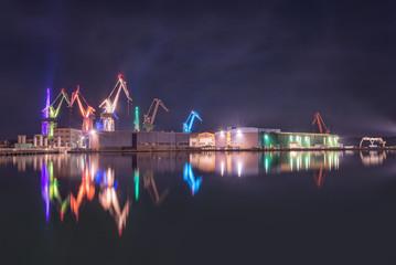 Illuminated cranes at shipyard in Pula