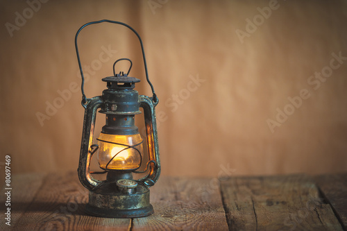 vintage kerosene oil lantern lamp burning with a soft glow light - 80697469