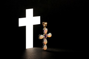 Golden Cross with gemstone jewel on black background
