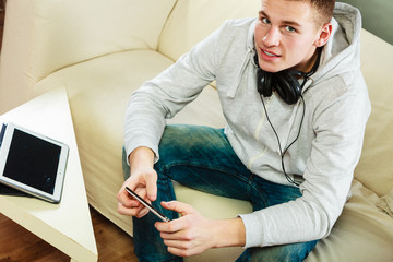 man on couch with headphones smartphone and tablet