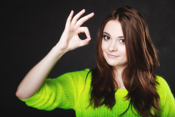 teen girl showing ok sign hand gesture on black