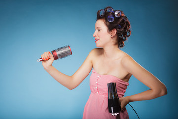 girl with curlers in hair holds hairdreyer