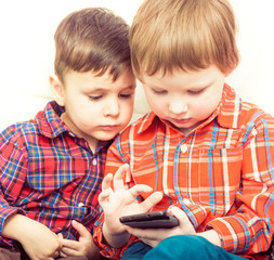 two kids using touch screen pone