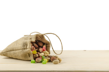 Different nuts and candied fruits in bag on the wooden table