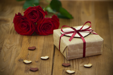 Red roses and gift box tied red ribbon with small wooden hearts