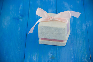 White gift box tied pink ribbon on blue wooden background