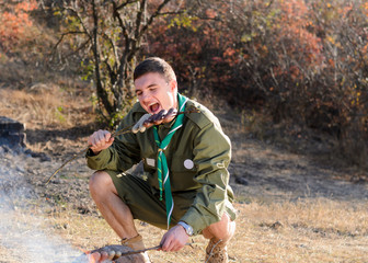 Boy Scout Eating Sausage on Stick by Campfire