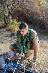 Boy Scout Cooking Sausages on Sticks over Campfire