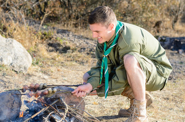 Boy Scout Cooking Sausages on Stick over Campfire