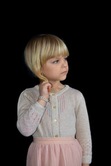 Thoughtful little girl on a black background