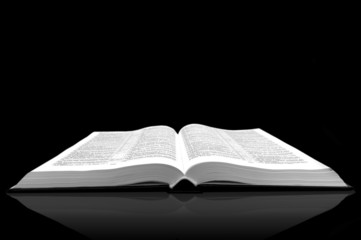 Open book bible on black background with shadow