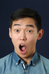 Astonished young Asian man looking at camera with opened mouth