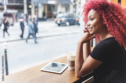 Fototapeta Beautiful girl in a cafe talking on smart phone