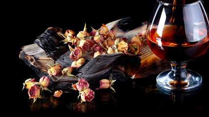 Red rose petals on books and bottle of wine.