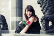 Happy young woman with a red rose sitting on the steps