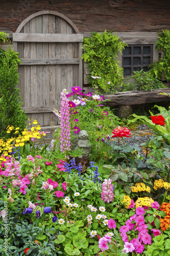 Landscaped backyard of a old house with flowering garden - 80708419