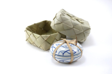 small ceramic container with woven box background isolated