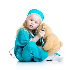 kid girl playing doctor with plush toy
