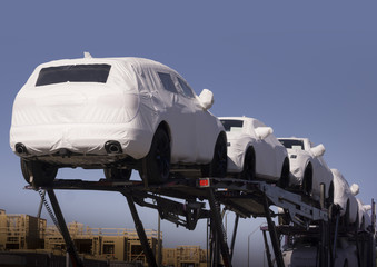 New auto cars under wraps being delivered on truck
