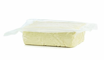 A vacuum packed block of tofu on a white background