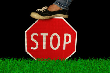 Stop sign in the grass held by someone's foot.