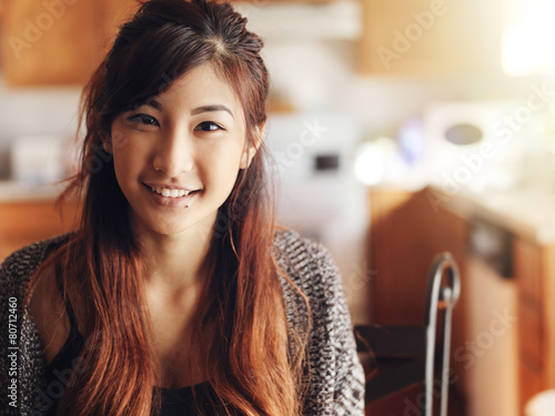 Leinwanddruck Bild happy smiling asian teen girl portrait in kitchen