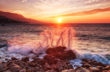 big sea wave breaks about a stone at sunrise