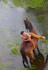 young sexy man with a naked torso lies on grain of  horse