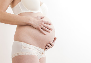 close up of standing pregnant woman wearing lingerie