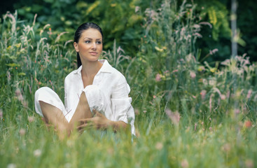 Young relaxing woman sitting in the grass