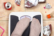Feet on bathroom scale with junk food garbage around - 80718429