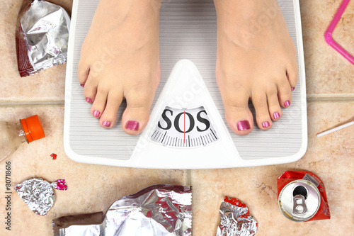 Feet on bathroom scale with word SOS and junk food garbage