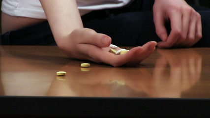 Woman suicide concept. Hand with pills on the table