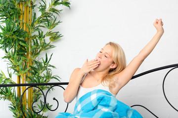 Frau streckt sich im Bett und gähnt