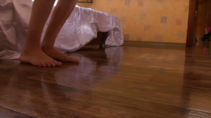 Young beautiful woman gets out of bed. View of the feet close-up