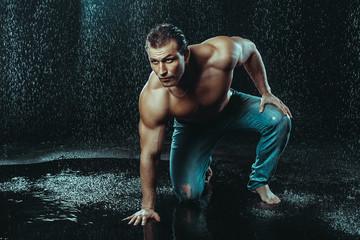 Strong Man Posing Under Rain Drops On Dark Background