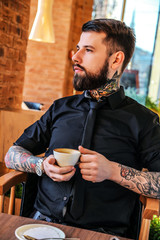 Tattoed man sitting in a cafe