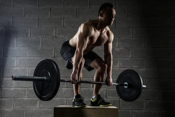 Man with naked torso holds barbell