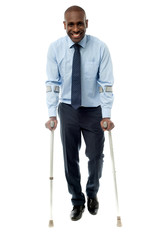 Middle aged man walking with two crutches