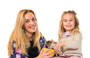 Mother and daughter playing with cup of coffee