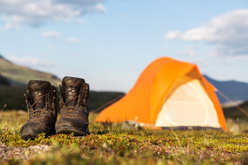 hiking boots in front of a tent
