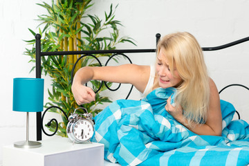 Frau im Bett schlägt nach dem Wecker