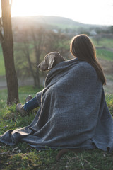 Woman with her beautiful dog lying outdoors