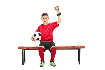 Delighted boy in soccer uniform holding a trophy