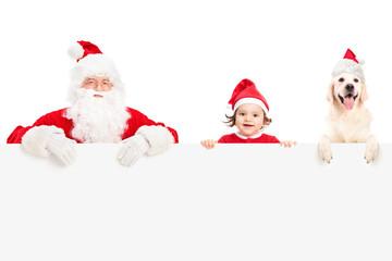 Santa, a baby girl and a dog posing behind panel