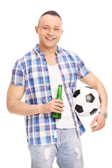 Young guy holding a bottle of beer and football