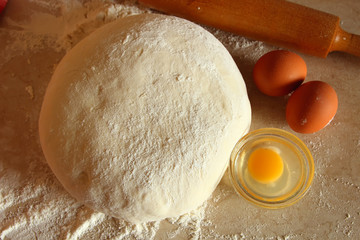 Yeast dough, eggs, and flour on the table, top view.