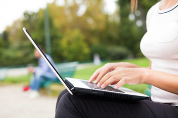 Woman using a laptop computer outdoors