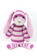 Knitted rabbit toy sitting over white background