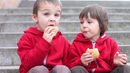 Two cute boys, eating donuts outdoor springtime